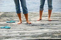 legs of girl 13 girl 18 standing on dock together
