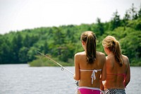 girl 13 with girl 18 fishing together on dock at cottage