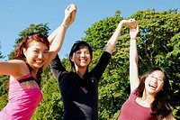 3 asian women standing together with arm in air