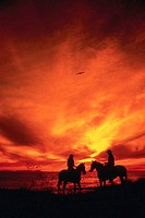 Cowboys Meeting at Sunset on Horseback