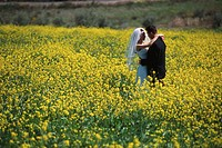 Newlyweds Hugging in Meadow