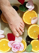 Foot on Orange Slices and Rose Petals