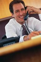 Smiling Businessman Using Telephone