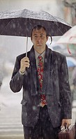 Businessman Standing in Rain Holding Umbrella