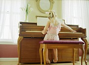 Little Girl in Ballet Outfit Playing Piano