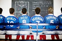 Soccer Team Studying Play on a Blackboard