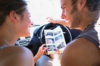 Couple in Car Looking at Brochure
