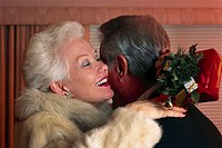 Woman Hugging Husband For Fur Coat Gift