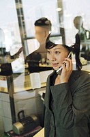 Businesswoman looking out the window, using mobile phone