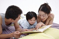 Family with one child lying on bed, reading book