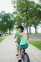 Couple cycling on tandem bicycle, woman looking over shoulder