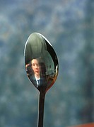 Reflection  Schoolgirl looking at her reflection in the convex back of a spoon  To see her reflection inverted when seen in the concave bowl of the sp...