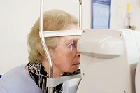 Eye measurements  Patient having her eyes scanned by an optical biometer  The beam of light seen passing across her right eye is scanning the eye to m...