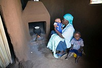 Improved ventilation  Mother sitting by a fireplace with her 1-year-old child and baby  The fireplace has been equipped with an adobe smoke hood and c...