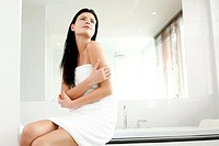 Woman in towel sitting on the bathtub ledge