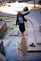 Businesswoman Wading in a Fountain
