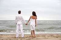 Sandy beach, couple, standing, hands hold, view from behind, gaze sea, summer,  Vacation, leisure time, 20-30 years, 30-40 years, clothing white, in l...