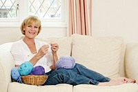 Senior woman sitting on the couch knitting