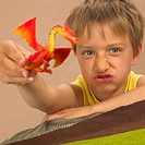 Child, boy, toy animal, shows,  Facial expression, portrait, truncated,   7 years, blond, toy, plastic dragon, fable animal, red-orange, games, holdin...