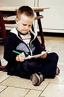 Boy sitting on the floor drawing