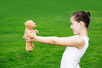 Girl holding up a toy bear (thumbnail)