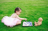 Little girl playing chess with toy bear