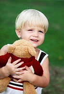 Little boy hugging a toy bear