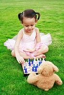 Little girl playing chess with teddy bear