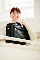 Businesswoman with a laptop bag looking at the camera (thumbnail)