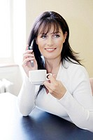 Woman holding a cup while talking on the mobile phone (thumbnail)