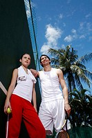Couple holding tennis racquet and tennis ball (thumbnail)