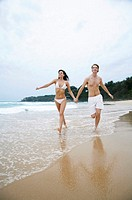 Couple holding hands while running on the beach