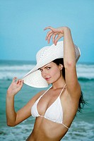 Woman in white hat and bikini posing for the camera