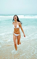 Woman in bikini running happily on the beach