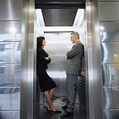 Businesswoman and Businessman Smiling at Each Other in Elevator (thumbnail)