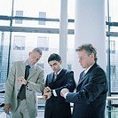 Group of three business men standing in office, looking at watch (thumbnail)