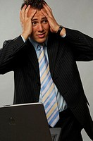 Businessman holding his head in distress (thumbnail)