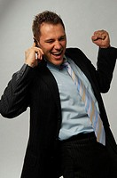 Triumphing businessman using mobile phone