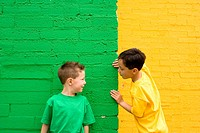 Two boys against yellow and green wall