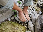 Feet resting next to the river. Espinama, Cantabria. Spain