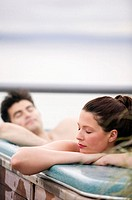 Young couple in hot tub, eyes closed