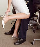 Businessman embracing secretary in office, low section, side view
