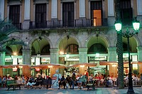 Visitors, in, pavement, cafe, at, arcades, of, Placa, Reial, at, night,, Barcelona,, Catalonia,, Spain