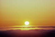 Hawaii, Sunball shining over clouds in golden yellow sunset sky
