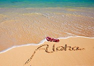 Hawaii, Turquoise ocean waters, foaming shore water, orchid lei, Aloha written in sand