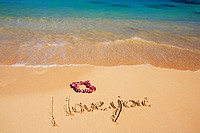 Hawaii, Turquoise ocean waters, foaming shore water, orchid lei, I love you written in sand