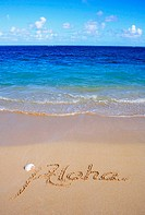 Hawaii, Turquoise ocean waters, foaming shore water, seashell, Aloha written in sand