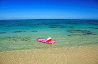 Pink inflated raft and beachball on clear ocean water