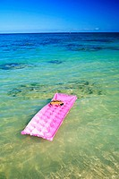 Snorkel and mask rest on pink inflated raft afloat on clear ocean water