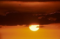Sun sinking behind clouds in a orange sunset sky, airplane in distance (thumbnail)